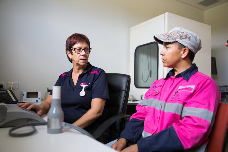 Health professional speaking to worker
